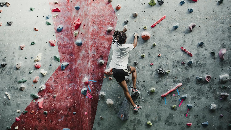 Nuori mies kiipeää ylöspäin kiipeilyseinällä