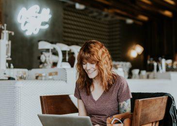 Nuori nainen kannettavan tietokoneen ääressä kahvilassa